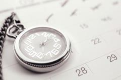 Vecchio orologio da tasca alla pagina del calendario annata, black&white immagini stock