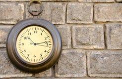 Vecchio orologio della via su una parete di pietra Fotografia Stock