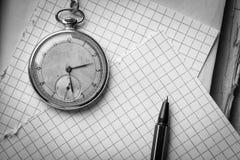 Vecchio orologio, pagine di carta in una gabbia, una penna su un libro saggio Concetto di formazione Fotografia Stock Libera da Diritti