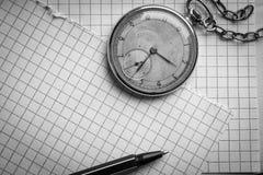 Vecchio orologio, pagine di carta in una gabbia, una penna su un libro saggio Concetto di formazione Fotografie Stock