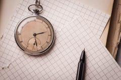 Vecchio orologio, pagine di carta, una penna su un libro saggio Concetto di formazione Immagini Stock Libere da Diritti