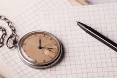 Vecchio orologio, pagine di carta, una penna su un libro saggio Concetto di formazione Fotografie Stock Libere da Diritti