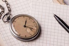 Vecchio orologio, pagine di carta, una penna su un libro saggio Concetto di formazione Fotografia Stock Libera da Diritti