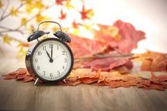 Vecchio orologio sulle foglie di autunno immagine stock