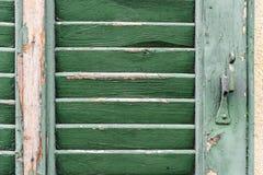 Vecchio otturatore di legno verde con il primo piano verde della pittura della sbucciatura Immagine Stock Libera da Diritti
