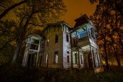 Vecchio palazzo frequentato abbandonato di legno terrificante alla notte immagine stock