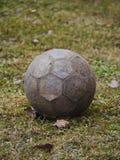 Vecchio pallone da calcio di cuoio su erba appassita Fotografie Stock