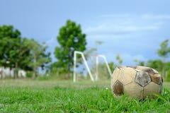 Vecchio pallone da calcio sgonfiato, vecchio calcio sgonfiato sull'erba verde Fotografia Stock