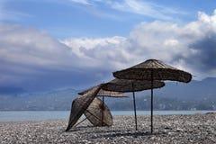 Vecchio parasole sulla spiaggia abbandonata Fotografia Stock