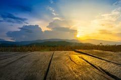 Vecchio pavimento di legno marrone accanto al campo agricolo nel tramonto del fascio e di sera Immagine Stock Libera da Diritti