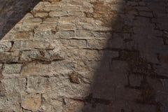 Vecchio pavimento di pietra del primo piano fra il sole e l'ombra all'alba per fondo fotografia stock