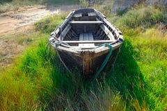 Vecchio peschereccio di legno sulla terra in erba alta nel centro di composizione Fotografia Stock