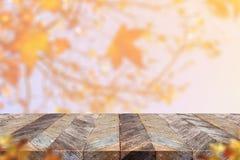 Vecchio piano d'appoggio di legno rustico vuoto della plancia con la foglia di acero della sfuocatura con Fotografia Stock