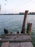 Vecchio pilastro di legno sul fiume vista dell'incrocio ad alta tensione del cavo il fiume Fotografie Stock Libere da Diritti