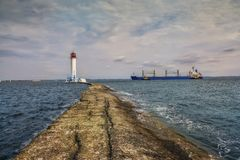 Vecchio pilastro di pietra che conduce al faro ed alla nave che entrano nel porto odessa l'ucraina Faro di Vorontsov fotografia stock
