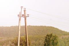 Vecchio pilone elettrico di legno inutile del ` s con i cavi rotti, tonificati fotografia stock libera da diritti