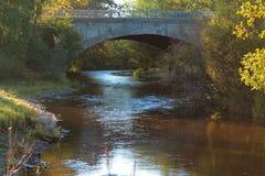 Vecchio ponte di pietra attraverso il piccolo corso d'acqua nel legno immagine stock