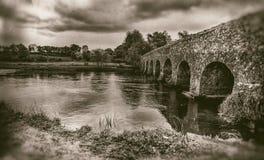 Vecchio ponte di pietra con gli arché, cielo lunatico, paesaggio nella seppia fotografie stock
