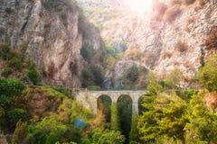 Vecchio ponte di pietra in montagne al tramonto Fotografia Stock