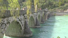 Vecchio ponte di pietra pedonale attraverso il fiume archivi video