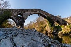 Vecchio ponte di pietra romano a Cangas de Onis immagini stock