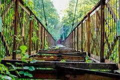 Vecchio ponte sospeso inutilizzato attraverso il burrone fotografia stock