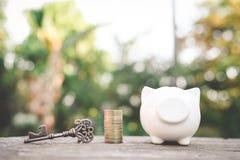 Vecchio porcellino salvadanaio chiave della moneta su legno Immagine Stock Libera da Diritti