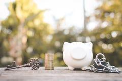 Vecchio porcellino salvadanaio chiave della moneta su legno Fotografie Stock Libere da Diritti