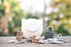 Vecchio porcellino salvadanaio chiave della moneta su legno un fondo del bokeh Immagini Stock Libere da Diritti