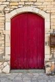 Vecchio portello rosso contro una vecchia parete di pietra Immagine Stock