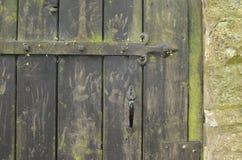 Vecchio portone di legno con le stampe della mano Immagini Stock