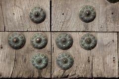 Vecchio portone di legno riparato con i grandi ribattini d'ottone Fotografie Stock Libere da Diritti