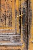 Vecchio primo piano giallo della porta con la maniglia Fotografia Stock