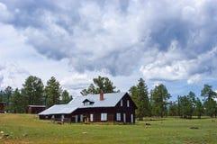 Vecchio ranch rustico della cabina della montagna sotto le nubi di tempesta Fotografie Stock
