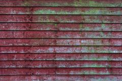 Vecchio recinto di legno rosso con i modelli verdi del muschio - struttura/fondo di lerciume di alta qualità immagine stock