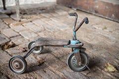 Vecchio retro triciclo dei bambini su un pavimento del mattone fotografie stock libere da diritti