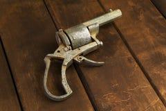 Vecchio revolver rotto sul bordo di legno Fotografie Stock Libere da Diritti