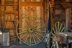 Vecchio ripristino aspettante giallo della ruota di vagone in un vecchio granaio immagine stock