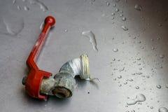 Vecchio rubinetto della crepa sul bagno del lavandino con acqua immagini stock libere da diritti