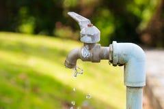 Vecchio rubinetto di vista laterale con acqua corrente con fondo confuso fotografia stock libera da diritti
