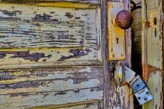 Vecchio, rustico, parzialmente porta aperta con il fermo rotto fotografia stock libera da diritti
