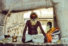 Vecchio sadhu che si siede nella posizione di loto in una delle tempie di Udaipur fotografia stock