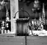 Vecchio secchio di acqua che si siede sul pozzo d'acqua a Williamsburg la Virginia fotografie stock libere da diritti