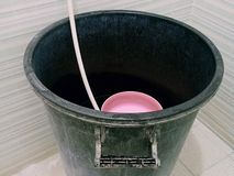 Vecchio secchio di plastica nero sporco di acqua in bagno fotografia stock libera da diritti