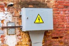 Vecchio segnale di pericolo ad alta tensione giallo che appende sulla scatola del metall Immagini Stock Libere da Diritti