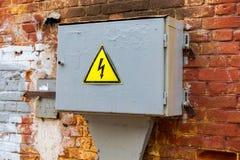 Vecchio segnale di pericolo ad alta tensione giallo che appende sulla scatola del metall Fotografia Stock Libera da Diritti