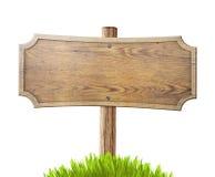 Vecchio segnale stradale di legno con erba isolata su bianco Fotografia Stock