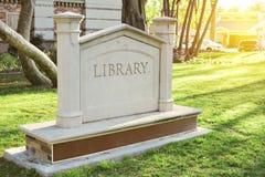 Vecchio segno concreto delle biblioteche con lo spazio della copia e l'illuminazione calda fotografia stock libera da diritti
