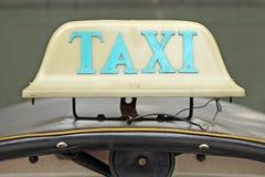 Vecchio segno del taxi sull'automobile della cima del tetto Immagine Stock