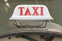 Vecchio segno del taxi sull'automobile della cima del tetto Fotografie Stock